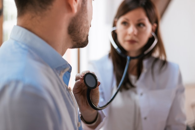 Young doctor is examining the patient with a stethoscope.