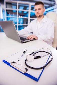 젊은 의사는 그의 사무실에서 일하고있다.