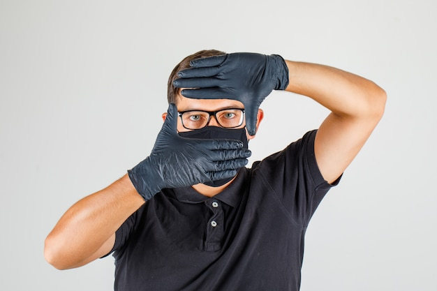 若い医者は黒のポロシャツに手でフレームジェスチャーを作る