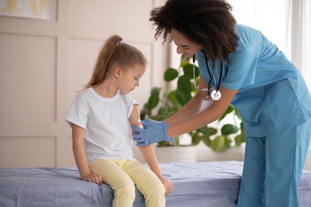 예방 접종 후 어린 소녀가 괜찮은지 확인하는 젊은 의사