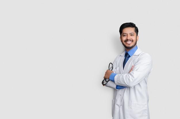 笑っている孤立した壁の上の若い医者の男性
