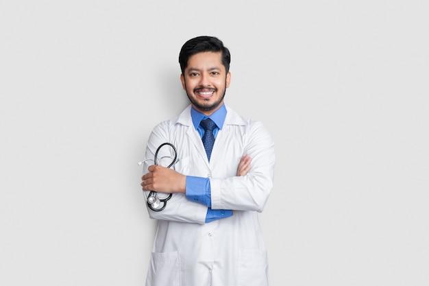笑顔の孤立した壁の上の若い医者の男性のクロスアーム