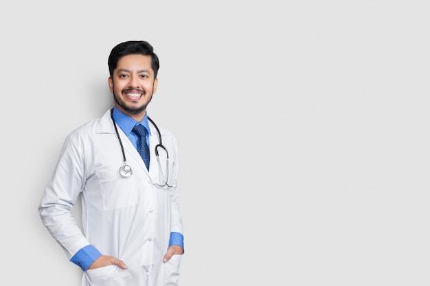 笑顔の孤立した壁の上のポケットに若い医者の男性の手