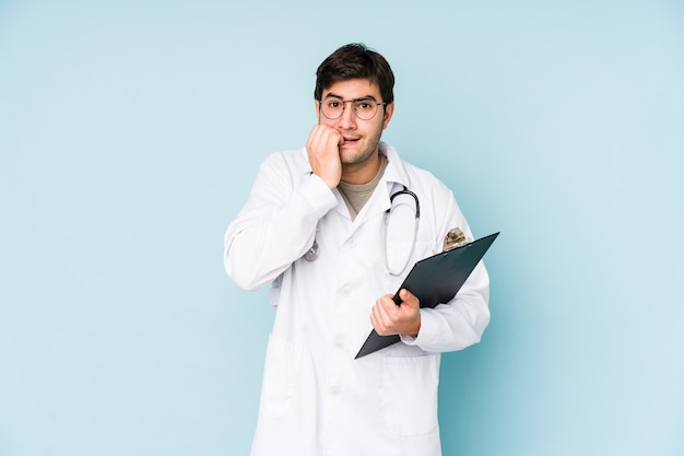 Young doctor man biting fingernails, nervous and very anxious.