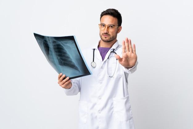 그녀의 손으로 중지 제스처를 만드는 흰색 배경에 고립 된 방사선을 들고 젊은 의사 남자