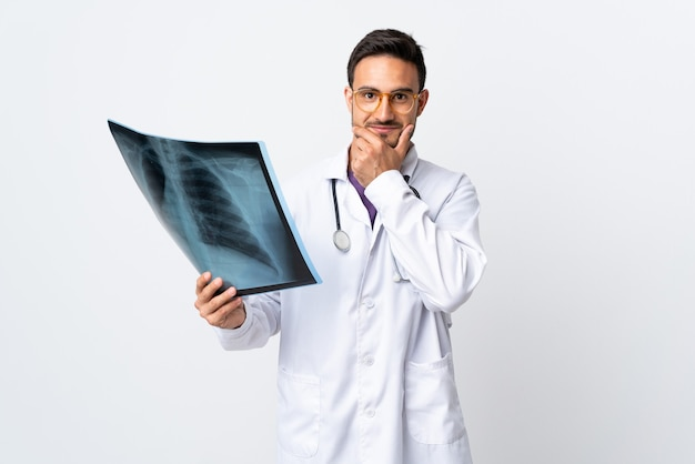 笑って白い壁に分離されたレントゲン写真を保持している若い医者の男