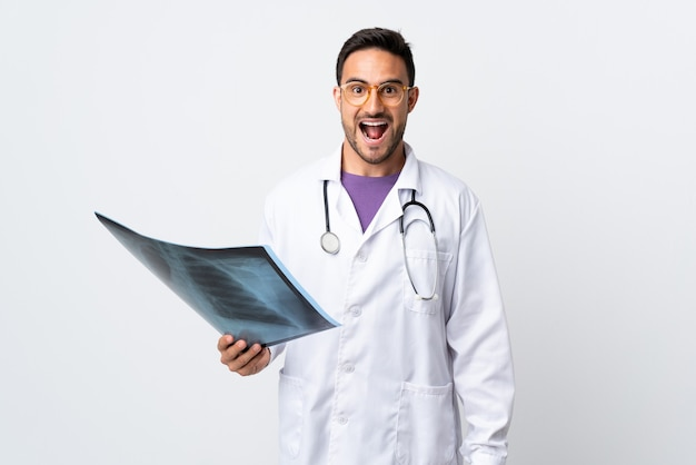 驚きの表情で白い壁に分離されたレントゲン写真を保持している若い医者の男