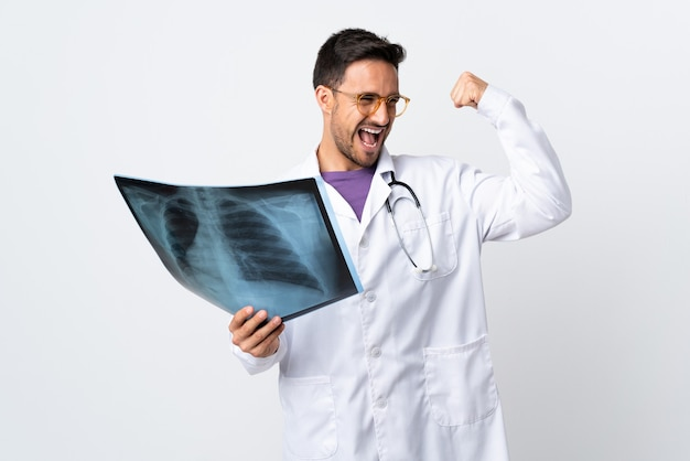 Young doctor man holding a radiography isolated on white celebrating a victory