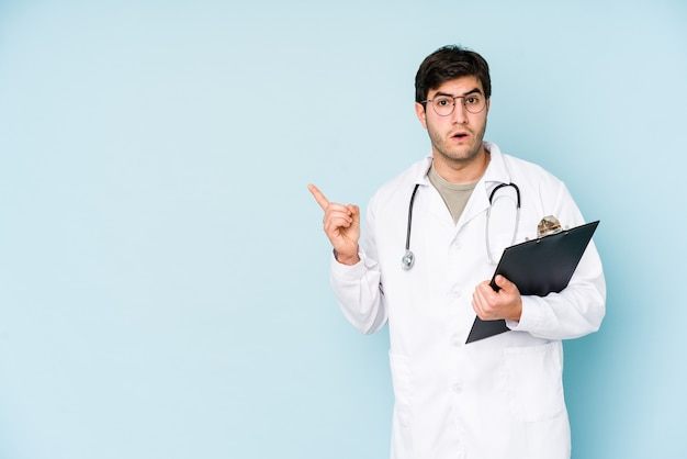 Young doctor man isolated on blue pointing to the side