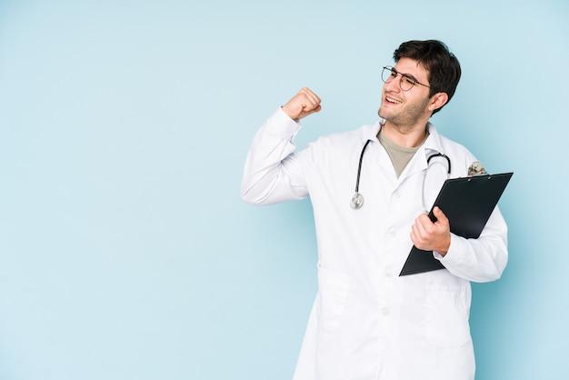 Молодой доктор человек, изолированные на синем фоне, поднимая кулак после победы, концепции победителя.