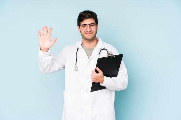 若い医者の男は、指で5番を示す陽気な笑顔の青い背景に分離されました。