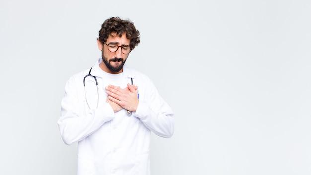 Молодой врач выглядит грустным, обиженным и убитым горем, держит обе руки близко к сердцу, плачет и чувствует себя подавленным у стены копировального пространства