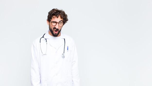 ショックを受けた、怒っている、イライラした、または失望した若い医者は口を開けて、コピースペースの壁に激怒