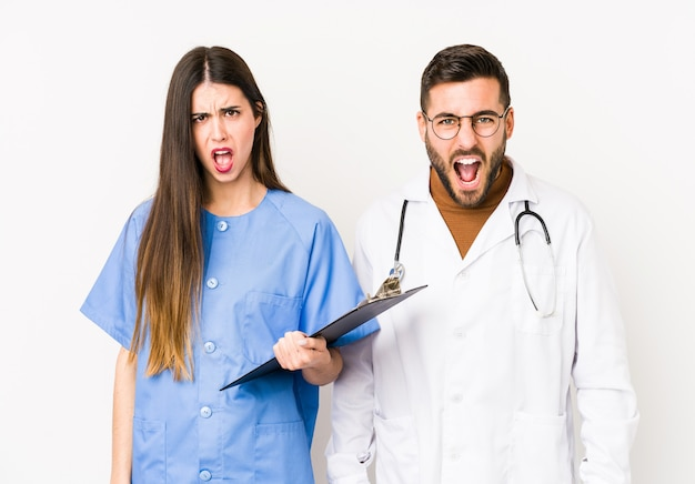 Young doctor man and a nurse isolated screaming very angry and aggressive.