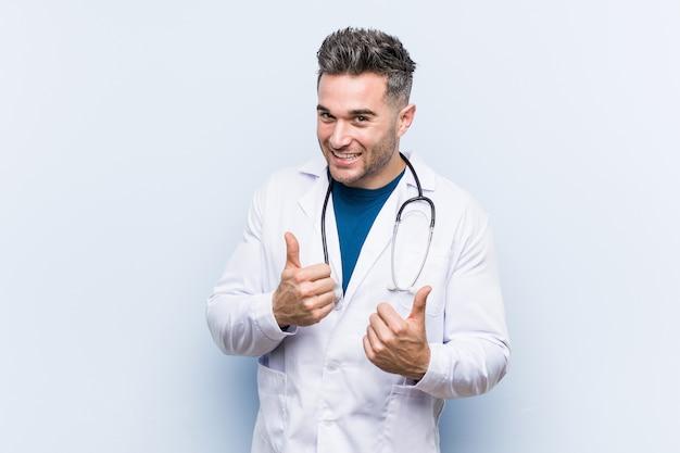 Молодой доктор мужчина поднимает пальцы вверх