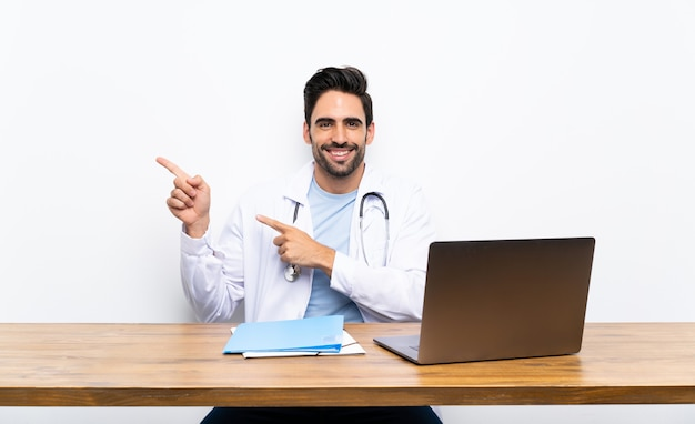 Young doctor man with his laptop over isolated wall pointing finger to the side