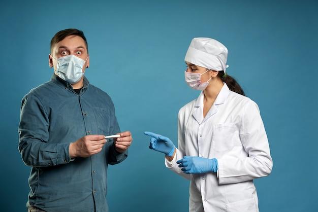 若い医者が温度計、青い壁で撮影スタジオで患者の温度を測定