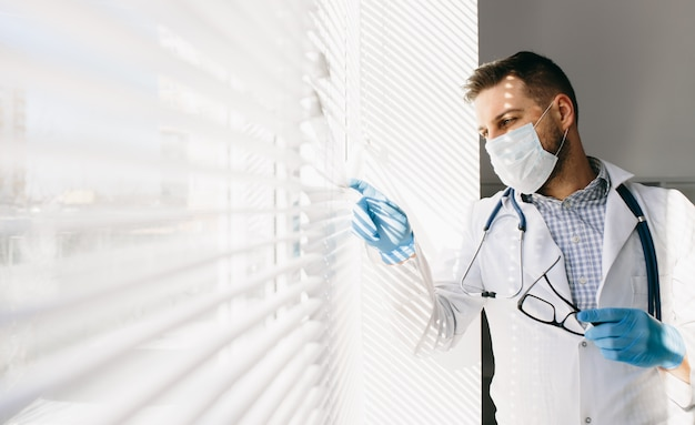 Young doctor in medical mask and gloves looking through window