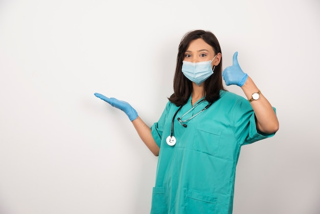 Young doctor in medical mask and gloves making thumbs up on white background. high quality photo