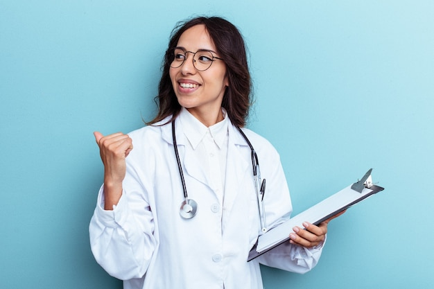 Young doctor mexican woman isolated on blue background points with thumb finger away, laughing and carefree.