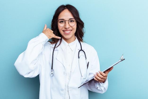 指で携帯電話の呼び出しジェスチャーを示す青い背景で隔離の若い医者メキシコの女性。