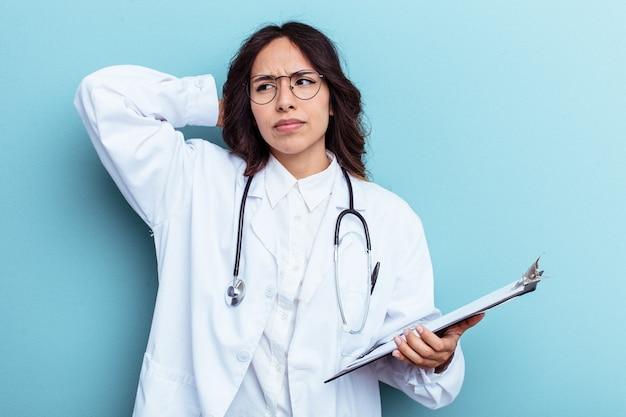 頭の後ろに触れて、考えて、選択をする青い背景で隔離の若い医者メキシコの女性。
