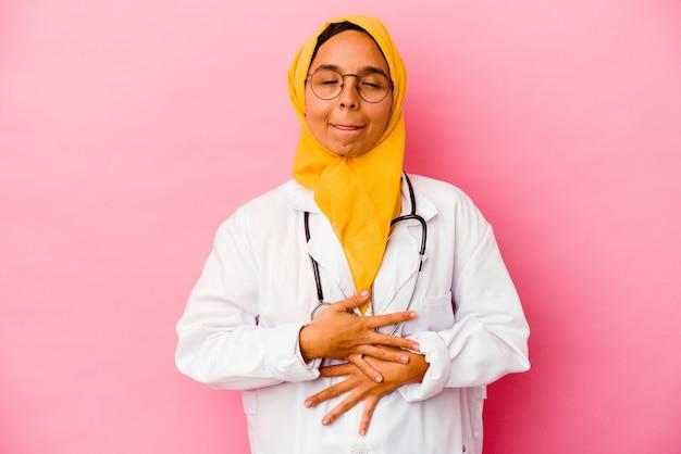 ピンクの背景で隔離の若い医者のイスラム教徒の女性はおなかに触れ、優しく微笑んで、食事と満足の概念。