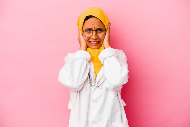 너무 시끄러운 소리를 듣지 않으려 고 손으로 귀를 덮고 분홍색 벽에 고립 된 젊은 의사 이슬람 여자