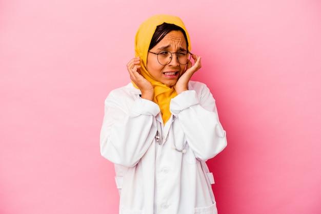 손으로 귀를 덮고 분홍색 벽에 고립 된 젊은 의사 이슬람 여성