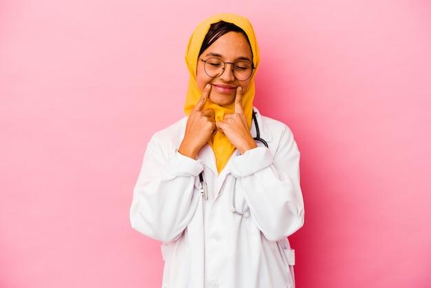 ピンクの壁に孤立した若い医者のイスラム教徒の女性は、2つのオプションの間で疑っています。