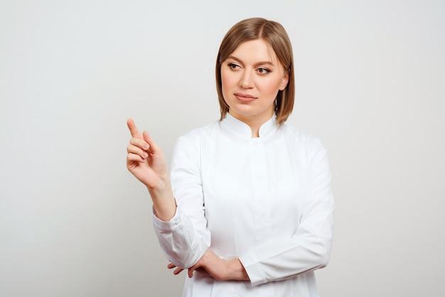 コピースペースを指す若い医者。白い白衣を着た魅力的な女医。治療療法治療法の概念。白い孤立した背景に制服を着た女医師。病院スタッフワーカー。
