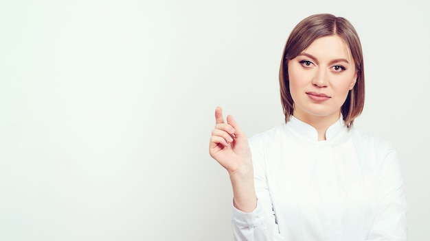 コピースペースを指す若い医者白い白衣の魅力的な女性医師