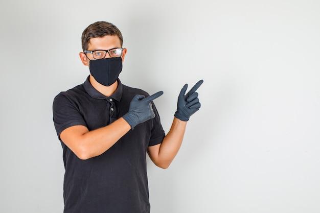 若い医者が黒のポロシャツで指を離れて指して注意深く見て