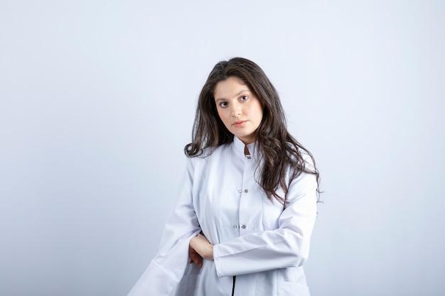 젊은 의사가 포즈를 취하고 흰 벽에 서 있습니다.
