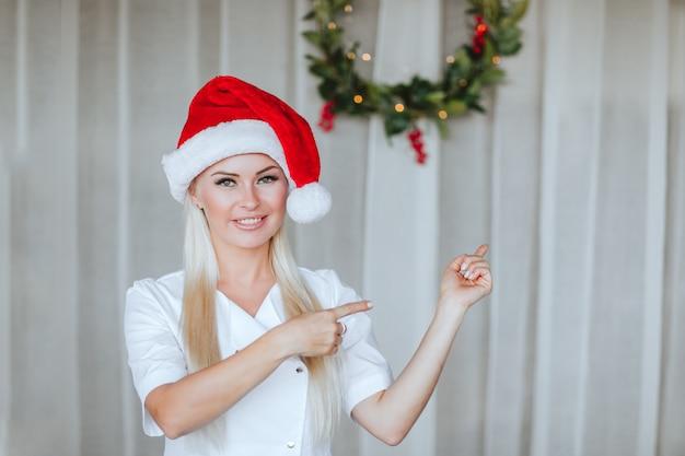 クリスマスの花輪と白い背景でポーズをとる若い医者。スペースをコピーします。
