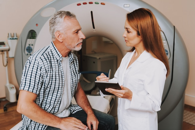Young doctor preparing grandfather for mri scan.