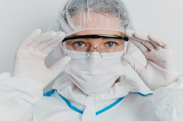 Young doctor putting on protective goggles