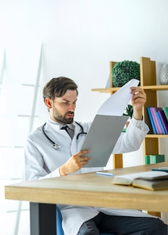 Young doctor reading notes on clipboard