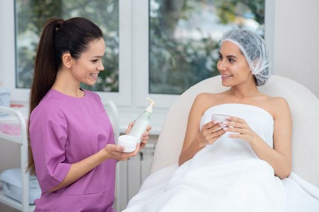 Молодой врач, рекомендующий косметику женщине