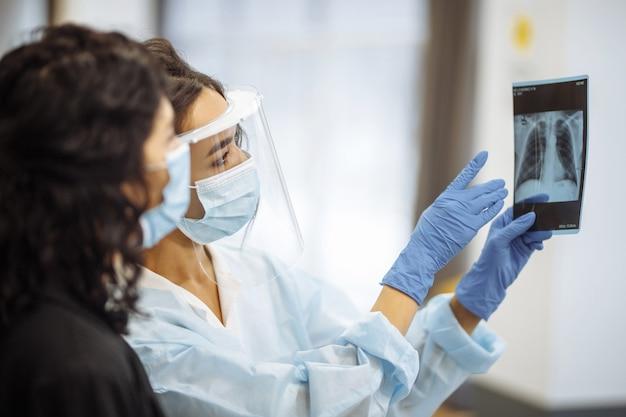 Молодой врач показывает пациенту рентгеновский снимок легких и объясняет диагноз. профилактика и профилактика коронавируса. концепция больницы и медицины.