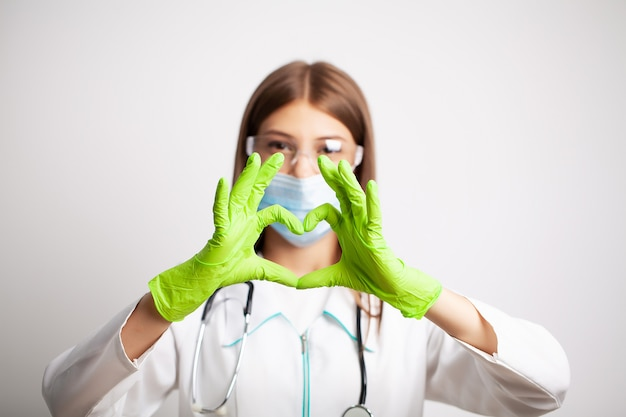 Young doctor shows a heart symbol in gloves