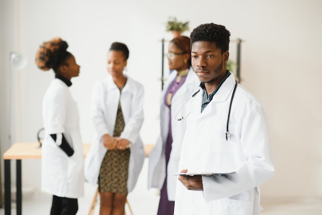 Young doctor smiling while standing in a hospital corridor with a diverse group of staff