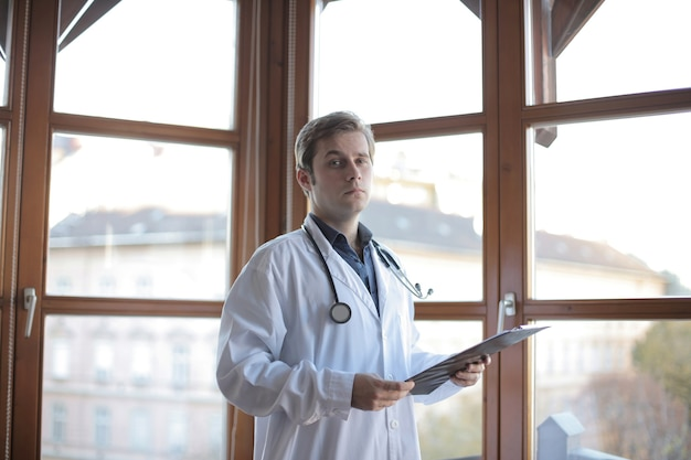 Young doctor standing in his office with windows on the background