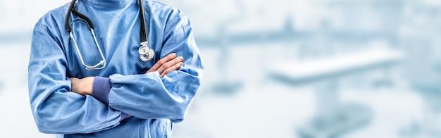 메스와 젊은 의사 외과 전문의. 배경에서 수술실의 내부가 흐려졌습니다.