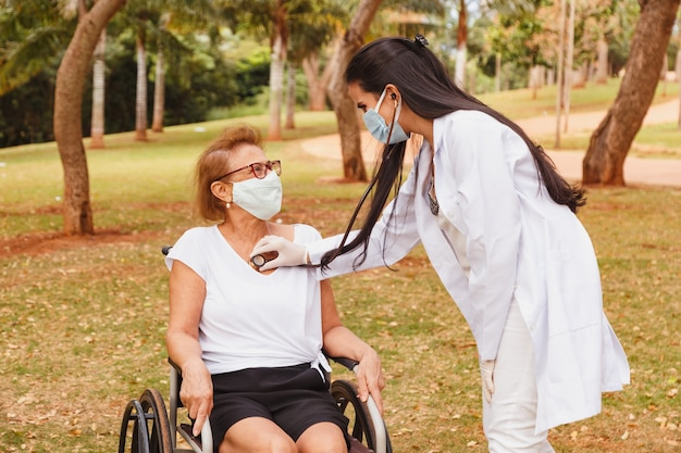 Young doctor taking care of an elderly woman in the park