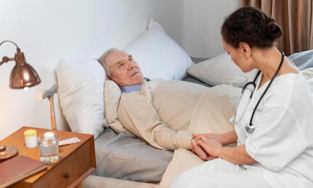 그녀의 노인 환자와 얘기하는 젊은 의사