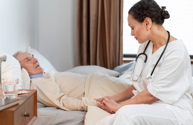 Young doctor talking with her senior patient