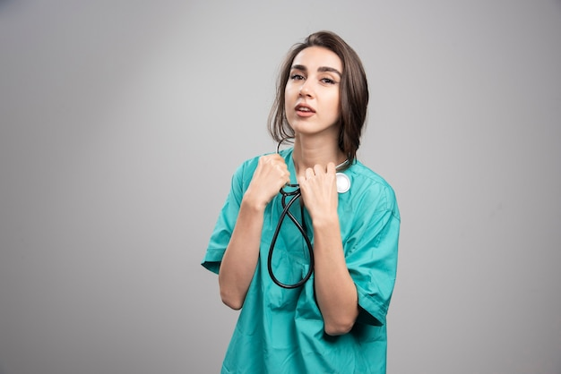 Young doctor in uniform using stethoscope on gray background. high quality photo