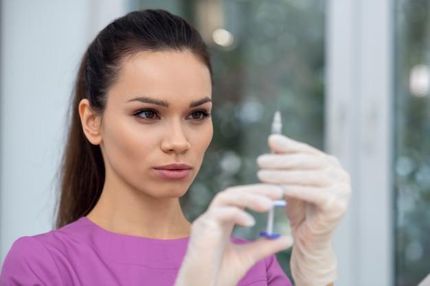 Молодой врач с помощью шприца в клинике