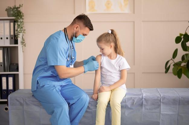 어린 소녀를 예방 접종하는 젊은 의사